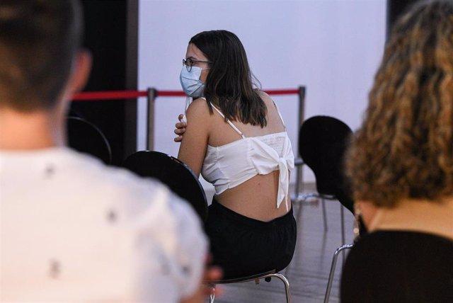 Una adolescente espera en una sala, después de recibir la primera dosis de la vacuna Pfizer en el punto de vacunación de Xátiva, situado en el Hogar de los Jubilados, a 10 de agosto de 2021, en Xátiva, Valencia, Comunidad Valenciana (España).