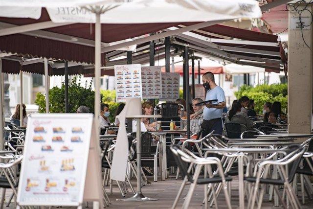 Un camarero atiende a varios clientes en la terraza de un bar en la Plaza Mayor de Ciudad Real, a 11 de agosto de 2021, en Ciudad Real, Castilla-La Mancha, (España).