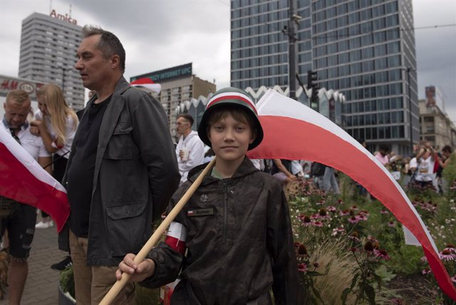 01 August 2021, Poland, Warsaw: A boy wearing a WWII military helmet and holding a Polish flag takes part in the 77th anniversary of the Warsaw uprising, a major World War II operation, in the summer of 1944, by the Polish underground resistance, led by t