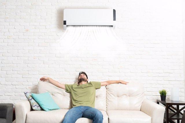 Archivo - Hombre disfrutando del aire acondicionado