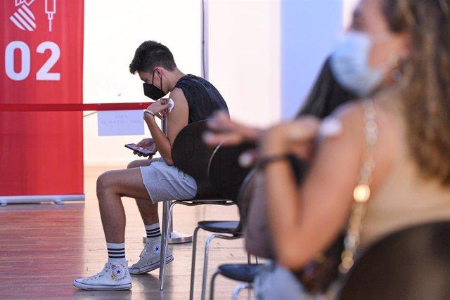 Un adolescent espera en una sala, després de rebre la primera dosi de la vacuna Pfizer en el punt de vacunació de Xátiva, situat en la Llar dels Jubilats, a 10 d'agost de 2021, en Xátiva, València, Comunitat Valenciana (Espanya).