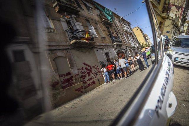 Personas ante los edificios de la Cruz Cubierta de València en riesgo de derrumbe