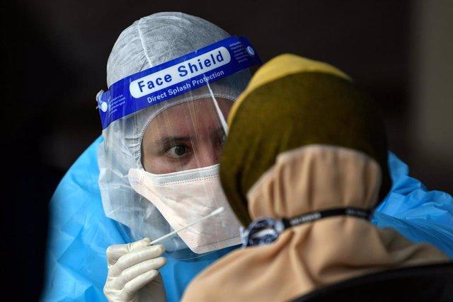 Un profesional sanitario practica una prueba de detección del coronavirus.