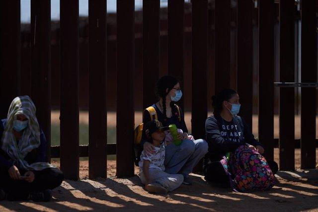 Archivo - Migrantes solicitantes de asilo se entregan a la Patrulla Fronteriza de Estados Unidos en el muro con México en Yuma.