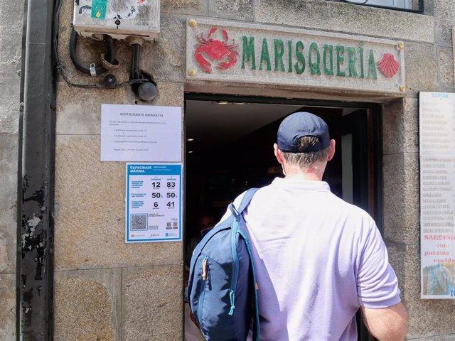 Varias indicaciones de obligatoriedad de presentar certificados antes de acceder al interior, en una marisquería de la Rua do Franco, en Santiago.