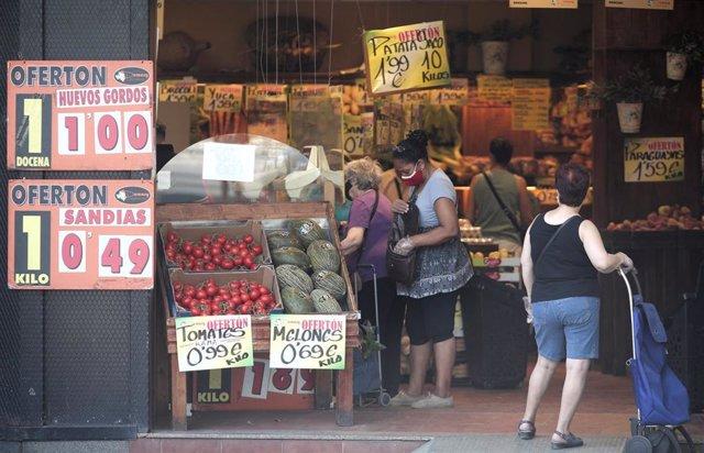 Archivo - Varias personas compran en una frutería