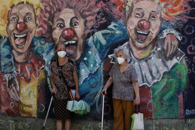 Archivo - Dos mujeres con mascarilla ante un mural en Caracas