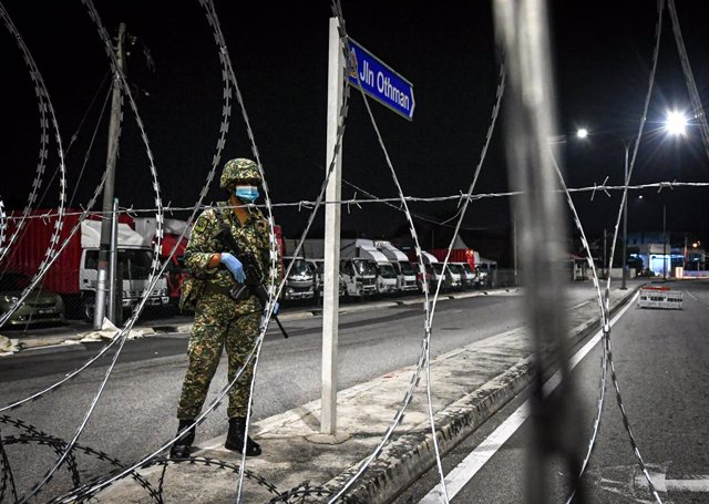 Archivo - 10 May 2020, Malaysia, Petaling Jaya: An Army member stands behind barbed wire fences in the Othman Road Market area. Restrictions aimed at reducingthe spread of the new coronavirus in Malaysia will remain in place for another month. Photo: Isk