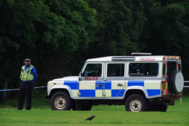 03 August 2021, United Kingdom, Bridgend: A police officer stands at a cordoned-off crime scene, where a five-year-old boy was found dead in the Ogmore River on Saturday. Photo: Ben Birchall/PA Wire/dpa