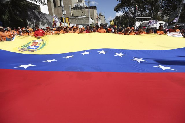 Archivo - 10 February 2020, Venezuela, Caracas: Supporters of the government of incumbent Venezuelan President Nicolas Maduro march with a large Venezuelan flag during a protest against the announcement of new sanctions by the United States against teh st