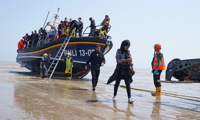 20 July 2021, United Kingdom, Dungeness: A group of people thought to be migrants crossing from France are brought ashore by the local lifeboat at Dungeness, after a small boat incident in the English Channel. Photo: Gareth Fuller/PA Wire/dpa