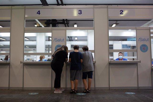 Dos adolescents acudeixen a rebre la vacuna contra el Covid-19 en el recinte de Montjuïc de Fira de Barcelona, a 4 d'agost de 2021, a Barcelona.