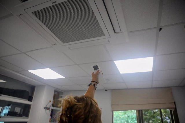Una mujer enciende el aire acondicionado en una oficina.- Archivo