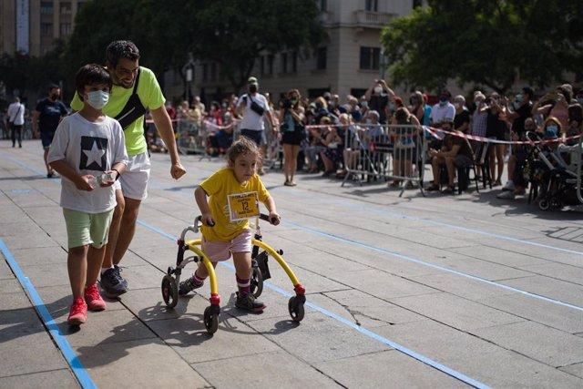 Una nena participa en la primera carrera infantil adaptada de les festes de Sant Roc del barri Gòtic de Barcelona.