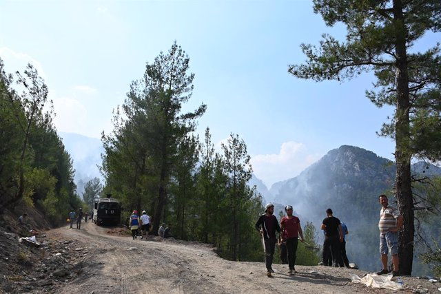 07 August 2021, Turkey, Koeycegiz: Helpers stand on a forest path while smoke rises in the background over the landscape of the community in the western Turkish town of Mugla. Ten days ago, fires broke out in numerous provinces across Turkey. Vast areas o