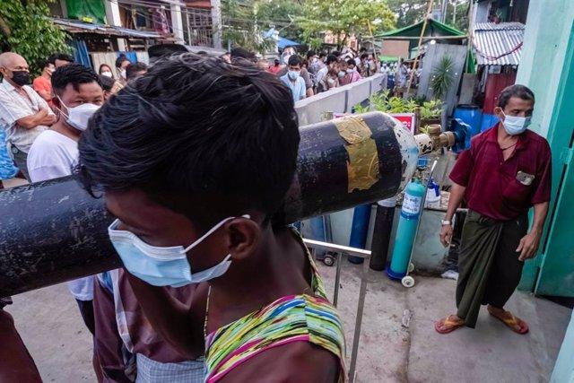 Decenas de personas hacen cola en Birmania para rellenar las bombonas de oxígeno.