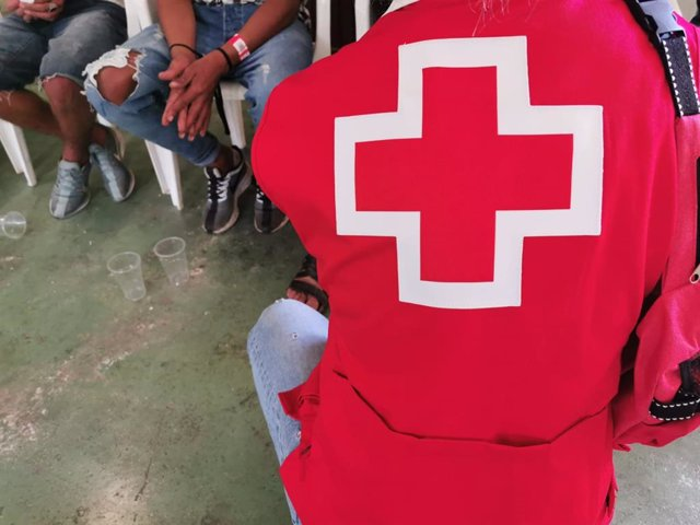 Archivo - Un voluntario de Cruz Roja atiende a personas llegadas en patera, en una imagen de archivo