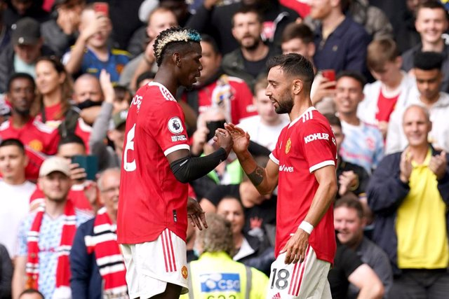 14 August 2021, United Kingdom, Manchester: Manchester United's Bruno Fernandes (R) celebrates scoring their side's first goal of the game with teammate Paul Pogba during the English Premier League soccer match between Manchester United and Leeds United a