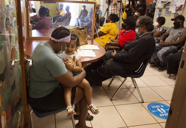 Archivo - 24 May 2021, US, Miami: Julie Jean (L), an undocumented immigrant from Haiti, holds her 2-year-old daughter, Maria J. Tellez while listening to a press conference regarding the Biden administration's redesignation of Temporary Protected Status (