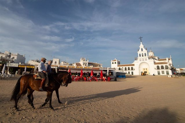 Archivo - Dos jinetes pasan por delante del Santiario de El Rocío, en una imagen de archivo.