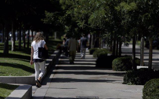 Algunas personas caminando por las calles del Paseo de Recoletos de Madrid en plena ola de calor.
