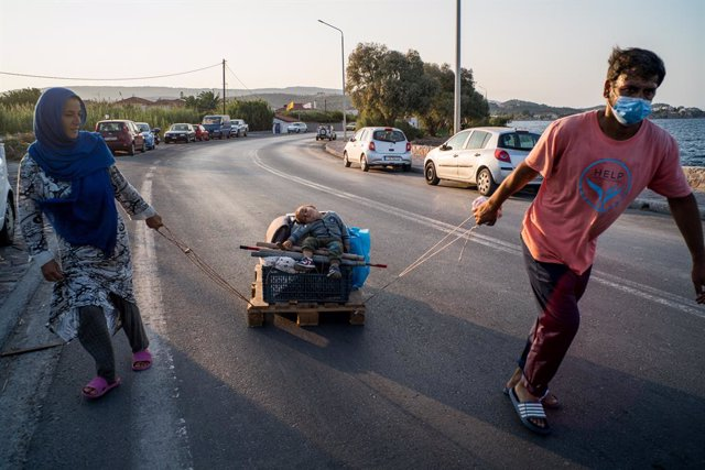 Archivo - Two Afghan parents move their few remaining belongings from the old camp in Moria with their baby on a pallet as a cart, in Lesbos, Greece, on 21 September 2020. Greece started yesterday to move 700 migrants from Lesbos to Athens after they went