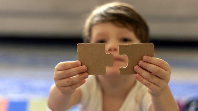 Archivo - Niño con utismo sujetando un puzzle