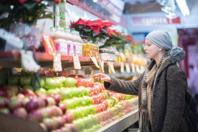 Archivo - Mujer con cáncer en el mercado comprando fruta.