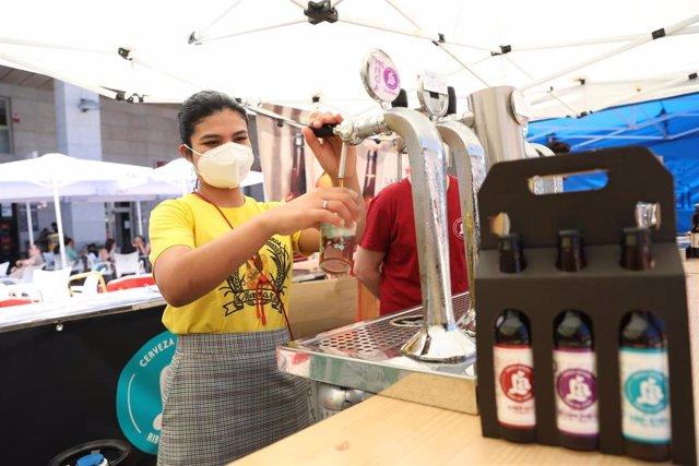 Archivo - Una camarera sirve un tubo de cerveza, en las instalaciones del Leganés Beer Festival