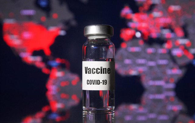Archivo - 21 November 2020, Ukraine, ---: A vial written on it coronavirus (COVID-19) vaccine is pictured in front of a map of the COVID-19 cases of the world.
