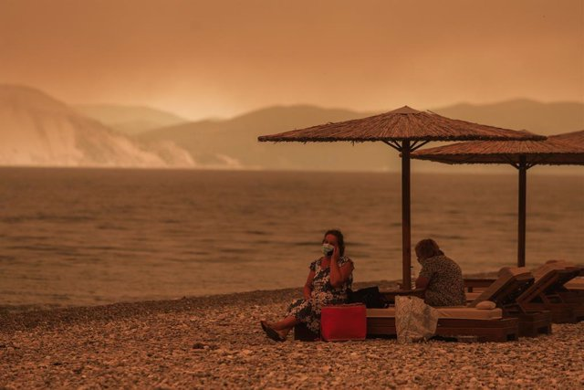 08 August 2021, Greece, Gouves: Two people sit on deck chairs on a smoke-shrouded beach near the village of Gouves on the island of Euboea. Photo: Eurokinissi/Eurokinissi via ZUMA Press Wire/dpa