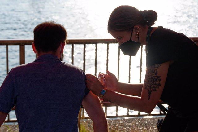 12 August 2021, North Rhine-Westphalia, Cologne: A man gets vaccinated at the Coronavirus vaccination station on the Rhine in the access area of the Folk music festival in Cologne. Visitors can spontaneously get vaccinated there with vaccines from Biontec