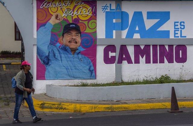 Archivo - Una mujer pasa ante un mural de Daniel Ortega en Managua