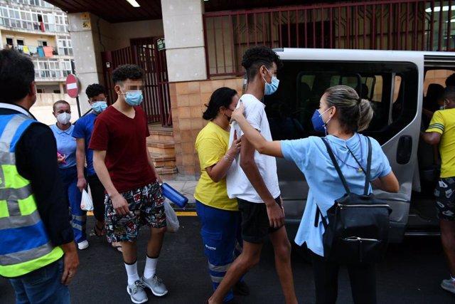 Trabajadores ayudan a tres de los menores marroquíes a las puertas del juzgado tras presentar una denuncia solicitando habeas corpus minutos antes de ser repatriados a su país de origen, en la frontera de Tarajal, a 16 de agosto de 2021, en Ceuta (España)