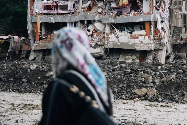 14 August 2021, Turkey, Bozkurt: A woman walks past debris after floods in Turkey's Black Sea region. At least 55 died after major flooding in northern Turkey. The three provinces of Bartin, Kastamonu and Sinop are particularly affected. Photo: Sedat Elba