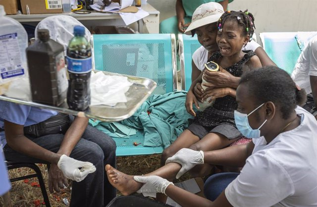 16 August 2021, Haiti, Les Cayes: A young girl is held by her mother as nurses care for a wound on her foot at OFATMA Hospital, as the patients afraid of hospital collapse after it's walls and floor cracked during the earthquake. Rescuers in Haiti are wor