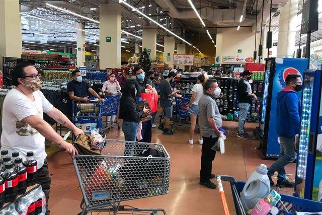Archivo - Gente esperando la cola para pagar en Walmart