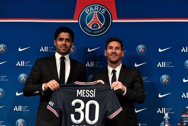 11 August 2021, France, Paris: Paris Saint-Germain's Qatari President Nasser Al-Khelaifi (L) poses along side Argentinian football player Lionel Messi as he holds-up his number 30 jersey during a press conference at the French football club Paris Saint-Ge