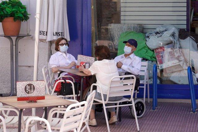 Ancianos con mascarilla conversan sentados en la terraza de un bar, a 27 de julio de 2021, en Madrid, (España).