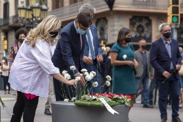 Illa diposita flors blanques en l'aniversari dels atemptats