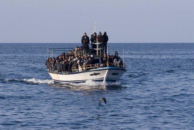Un grupo de personas en una embarcación cruza el Mediterráneo rumbo a las costas de Italia