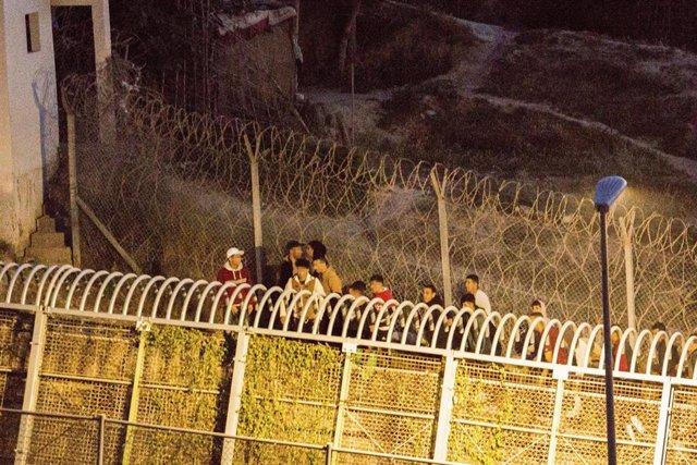Archivo - Varios marroquíes intentan llegar a suelo español desde la frontera que separa Melilla y Marruecos