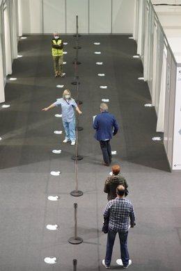 Archivo - Varias personas acuden a un dispositivo de vacunación contra la COVID-19 en el Bilbao Exhibition Center (BEC).