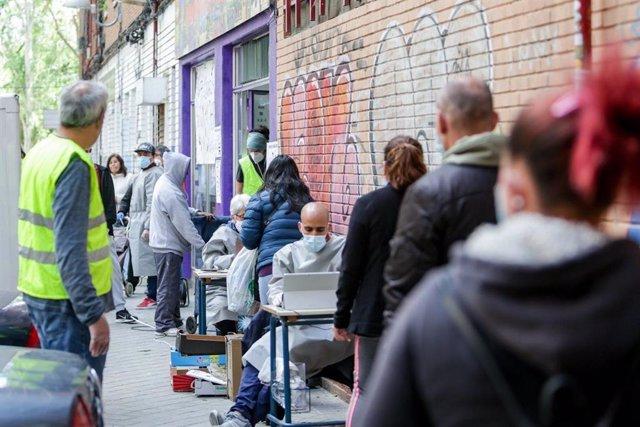 """Archivo - Cientos de personas sin recursos hacen cola en Aluche en busca de """"una bolsa de comida""""."""