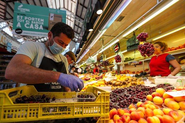 Archivo - Un hombre trabaja colocando la fruta en una una frutería del Mercado Central de Valencia después de que el Ministerio de Sanidad autorizara a que la totalidad de la Comunidad Valenciana pasase en su conjunto a la fase 1 de la desescalada, en Val