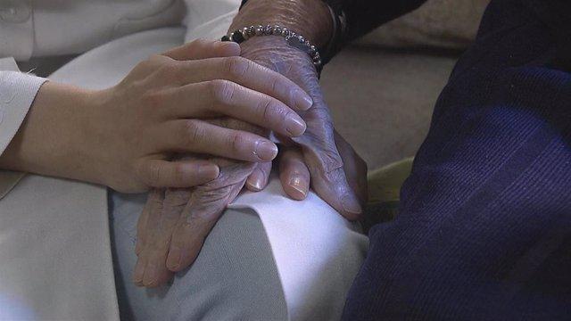 Las manos de un sanitario y su paciente.