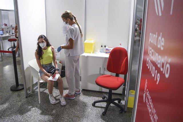 Una sanitaria vacuna a una adolescente con la primera dosis de la vacuna Moderna en la Ciudad de las Artes, a 16 de agosto de 2021, en Valencia, Comunidad Valenciana, (España).