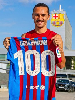 El jugador del FC Barcelona Antoine Griezmann posa con una camiseta con el dorsal '100' en conmemoración de sus 100 primeros partidos como blaugrana