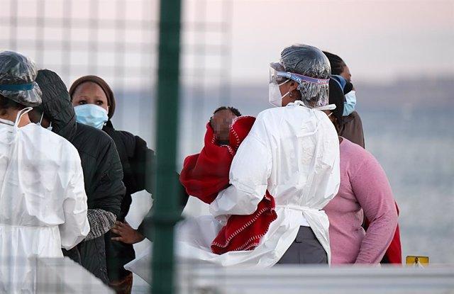 Archivo - Una sanitaria lleva en brazos a una niña que llega a tierra junto con otros migrantes tras el rescate del buque Salvamar Mizar a una patera de 56 inmigrantes subsaharianos, entre ellos dos bebés y es posible que alguna mujer embarazada, en el Pu
