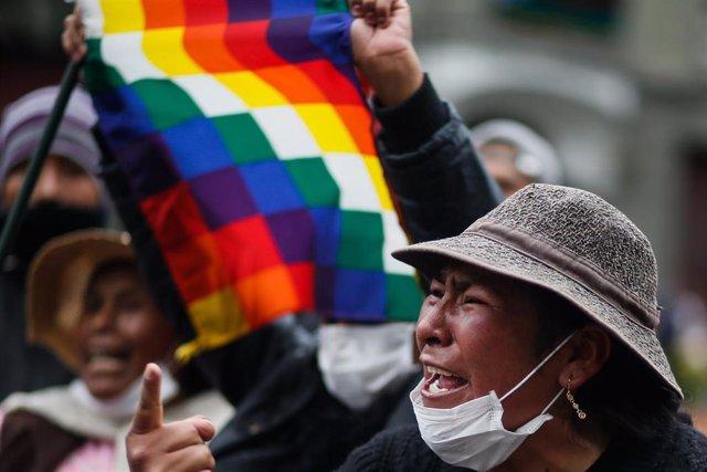 Archivo - Una seguidora de Morales con una bandera whipala durante las manifestaciones en Bolivia